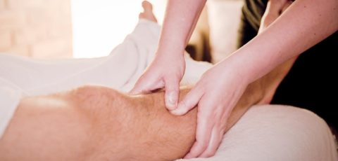 A practitioner performing sports massage on a clients leg at Clarity Massage and Wellness