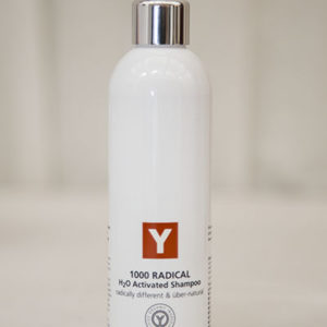 A bottle of Y natural's 1000 Radical, a H2o Activated Shampoo that is used at Clarity Massage and Wellness for their organic facials